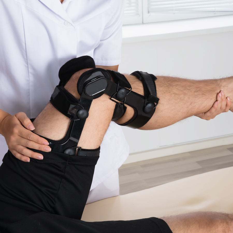 man lying on couch with knee brace receiving treatment from female physiotherapist
