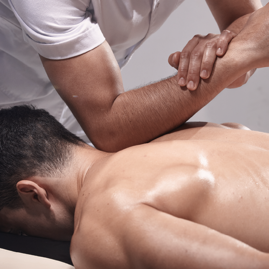 man face down on massage couch with therapist performing sports massage on his back using elbow